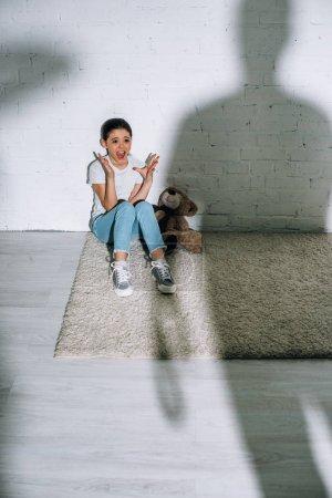 Photo pour Grande silhouette et gosse effrayé avec l'ours de nounours criant tout en s'asseyant sur le tapis - image libre de droit