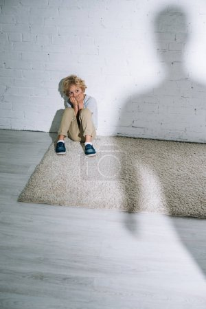Foto de Silhouette and scared little boy sitting on carpet - Imagen libre de derechos