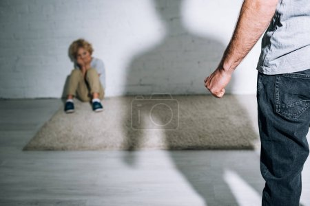 Photo for Partial view of abusive father and scared son sitting on carpet - Royalty Free Image
