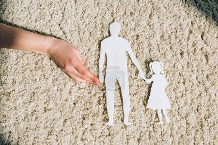 Foto de Vista parcial de la mujer con figuras de papel en la alfombra - Imagen libre de derechos