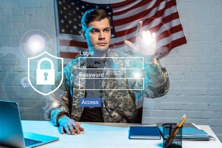 Photo pour Beau soldat en uniforme pointant avec le doigt à la connexion et le lettrage de mot de passe dans le bureau - image libre de droit