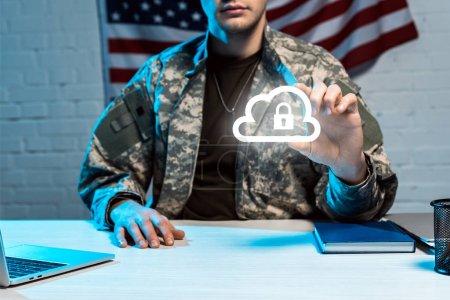 Photo pour Vue recadrée de l'homme militaire dans la gestuelle uniforme près du nuage avec le cadenas - image libre de droit