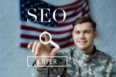 Photo pour Foyer sélectif de l'homme heureux dans l'uniforme militaire pointant avec le doigt au lettrage de seo - image libre de droit