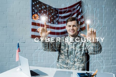 Photo pour Cheerful man in military uniform pointing with fingers at cyber security lettering - image libre de droit