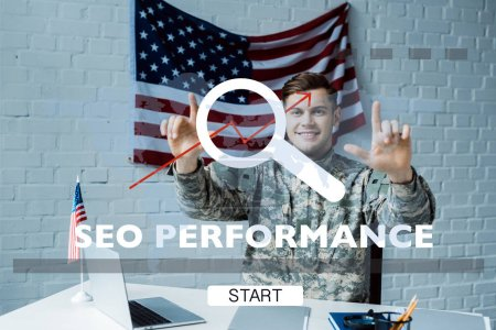 Photo for Cheerful man in military uniform pointing with fingers at seo performance lettering - Royalty Free Image