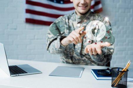 Photo pour Vue recadrée de l'homme heureux dans l'uniforme militaire pointant avec le doigt au nuage avec le cadenas - image libre de droit