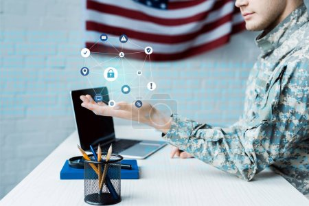 Photo for Cropped view of soldier gesturing near laptop with blank screen and data visualization - Royalty Free Image