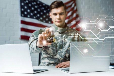 Photo pour Foyer sélectif de l'homme beau dans l'uniforme militaire retenant le cadenas métallique près des ordinateurs portables et du lettrage de gdpr - image libre de droit