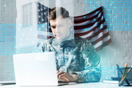 Foto de Handsome soldier in camouflage uniform using laptop in office near data visualization - Imagen libre de derechos