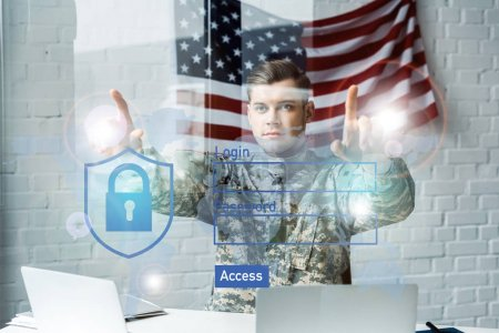 Foto de Handsome soldier in military uniform pointing with fingers at virtual access in office - Imagen libre de derechos
