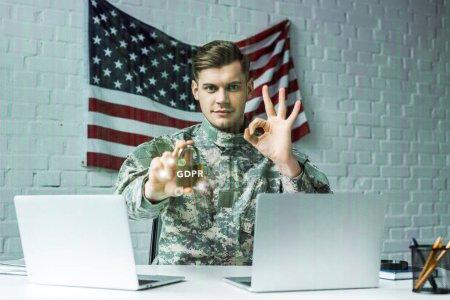 Photo pour Homme dans le cadenas de fixation militaire d'uniforme avec le lettrage de gdpr près des ordinateurs portables et montrant le signe ok - image libre de droit