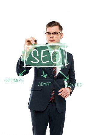 Photo pour Bel homme d'affaires dans des lunettes tenant stylo marqueur près de seo lettrage sur blanc - image libre de droit
