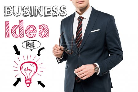 Photo for Cropped view of businessman in suit holding glasses near business idea lettering on white - Royalty Free Image
