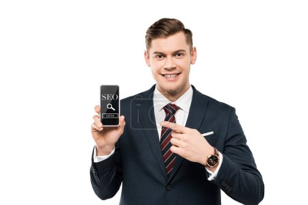 Photo pour Happy businessman in suit pointing with finger at smartphone with seo lettering on screen  isolated on white - image libre de droit