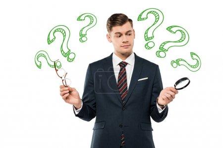 Foto de Handsome businessman holding glasses and magnifying glass and question marks on white - Imagen libre de derechos