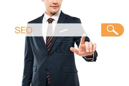 Photo pour Vue recadrée de l'homme heureux dans l'usure formelle pointant avec le doigt à la barre d'adresse avec le lettrage de séo sur le blanc - image libre de droit