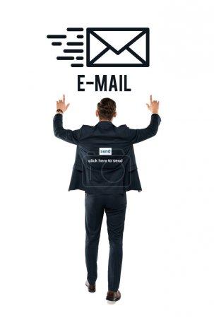 Photo pour Vue arrière de l'homme d'affaires pointant avec des doigts au lettrage d'e-mail tout en restant sur le blanc - image libre de droit