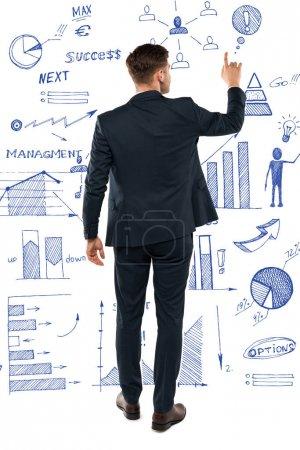 Photo pour Vue arrière de l'homme pointant avec le doigt tout en restant près des diagrammes et des graphiques sur le blanc - image libre de droit