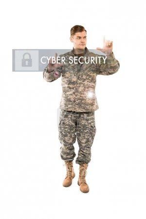 Photo pour Bel homme dans l'uniforme militaire pointant avec des doigts au lettrage de cybersécurité sur le blanc - image libre de droit
