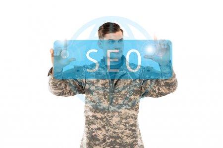 Photo pour Bel homme dans l'uniforme militaire pointant avec des doigts au lettrage de seo sur le blanc - image libre de droit