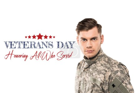 Photo for Serious and handsome soldier in uniform looking at camera near veterans day lettering on white - Royalty Free Image