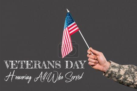 Photo pour Vue recadrée de soldat retenant l'indicateur américain près du lettrage de jour d'anciens combattants sur le gris - image libre de droit