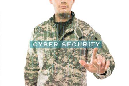 Photo pour Vue recadrée de soldat dans l'uniforme pointant avec le doigt au lettrage de cybersécurité sur le blanc - image libre de droit