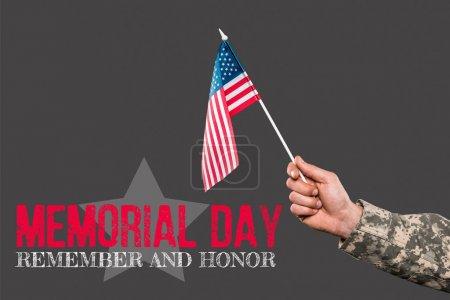 Foto de Vista recortada de soldado sosteniendo la bandera americana cerca del día conmemorativo letras en gris - Imagen libre de derechos