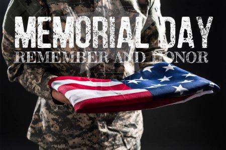 Photo pour Vue recadrée du soldat en uniforme de camouflage tenant le drapeau de l'Amérique près du jour commémoratif lettrage sur gris - image libre de droit