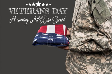 Photo for Cropped view of man in military uniform holding flag of america near veterans day lettering on grey - Royalty Free Image