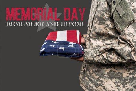 Photo pour Vue recadrée de l'homme en uniforme militaire tenant le drapeau de l'Amérique près du jour commémoratif lettrage sur gris - image libre de droit