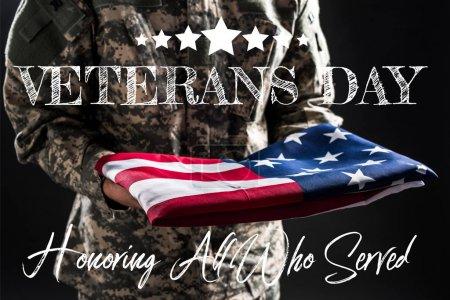 Photo pour Vue recadrée de soldat dans l'uniforme militaire retenant le drapeau de l'Amérique près du lettrage de jour d'anciens combattants sur le gris - image libre de droit