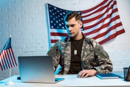 Foto de Apuesto soldado en uniforme usando portátil en la oficina - Imagen libre de derechos