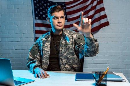 Foto de Apuesto soldado en uniforme sentado cerca de la computadora portátil y gesturing en la oficina - Imagen libre de derechos
