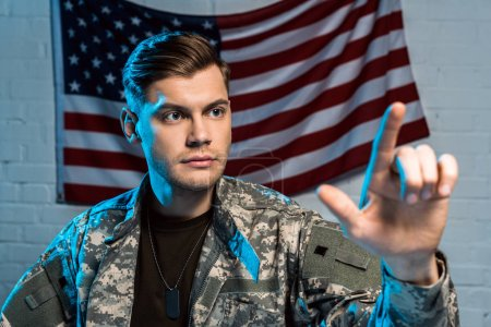Photo for Selective focus of handsome soldier pointing with finger near american flag - Royalty Free Image