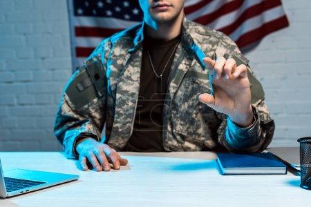 Photo pour Vue recadrée de l'homme militaire dans la gestuelle uniforme dans le bureau - image libre de droit