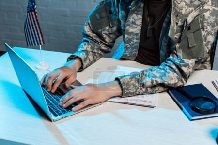 Photo for Cropped view of military man typing on laptop in office - Royalty Free Image