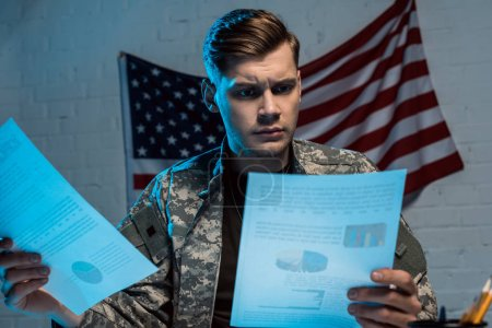 Photo for Handsome military man holding charts and graphs while sitting in office - Royalty Free Image