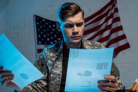 Photo pour Beau militaire tenant des diagrammes et des graphiques tout en s'asseyant dans le bureau - image libre de droit