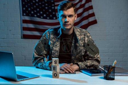 Photo pour Beau militaire s'asseyant avec les mains serrées près de l'ordinateur portatif et des cubes avec le lettrage de seo - image libre de droit