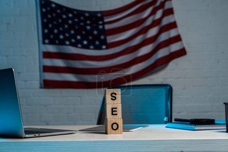 Photo pour Cubes avec le lettrage de seo près de l'ordinateur portatif et du drapeau américain dans le bureau moderne - image libre de droit