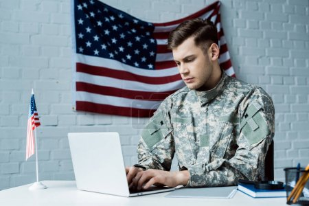 Photo for Young soldier in uniform using laptop in office - Royalty Free Image