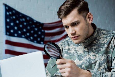 Foto de Vista de ángulo bajo de joven soldado en uniforme sosteniendo lupa cerca de la computadora portátil en la oficina - Imagen libre de derechos