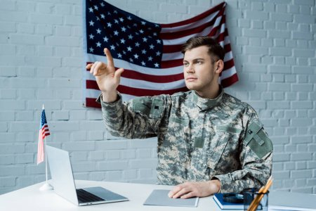 Photo for Handsome man in military uniform pointing with finger and sitting near laptop - Royalty Free Image