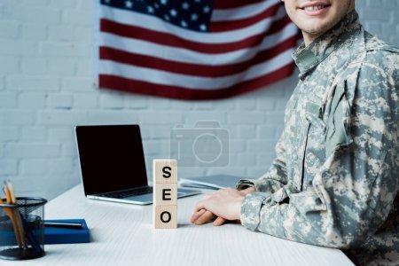 Photo pour Vue recadrée de soldat heureux près des cubes en bois avec le lettrage de seo et l'ordinateur portatif avec l'écran blanc - image libre de droit
