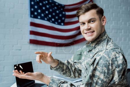 Photo pour Homme heureux de militaire faisant des gestes dans le bureau près de l'ordinateur portatif avec l'écran blanc - image libre de droit