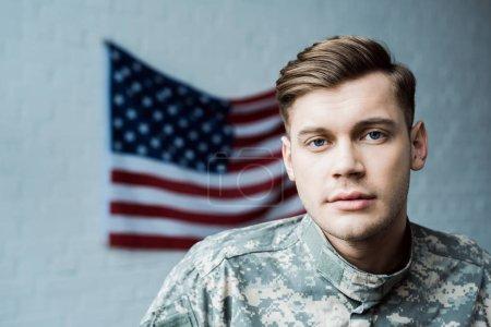 Photo pour Bel homme dans l'uniforme militaire regardant la caméra près du drapeau américain - image libre de droit