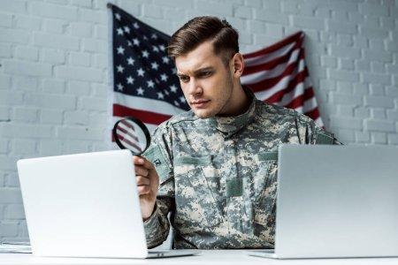 Photo pour Beau soldat retenant la loupe près des ordinateurs portables - image libre de droit