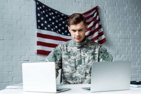 Photo pour Bel homme dans l'uniforme militaire utilisant des ordinateurs portatifs dans le bureau - image libre de droit