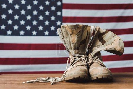 Photo pour Bottes militaires près du drapeau américain avec des étoiles et des rayures sur la surface en bois - image libre de droit